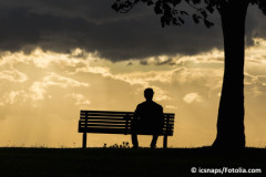 Silhouette of an anonymous male alone on a bench at sunset